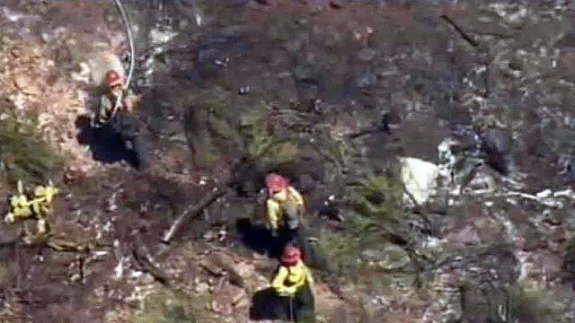 Firefighters extinguish hot spots after a fatal plane crash at Sedona Airport on Thursday morning.