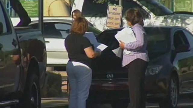 Rosemarie Friend, right, passes out fliers warning of a sex offender who is legally living near a school.