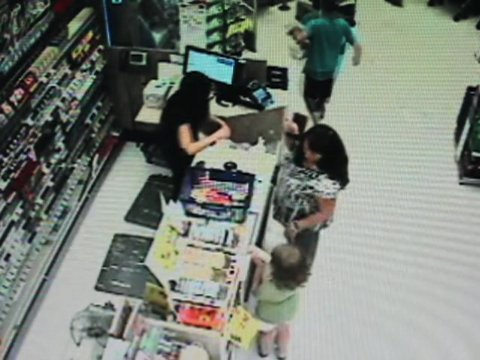 Surveillance photo of man taking donation jar.