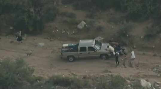 People try to help push a stuck vehicle that tried off-roading to avoid the traffic backup.