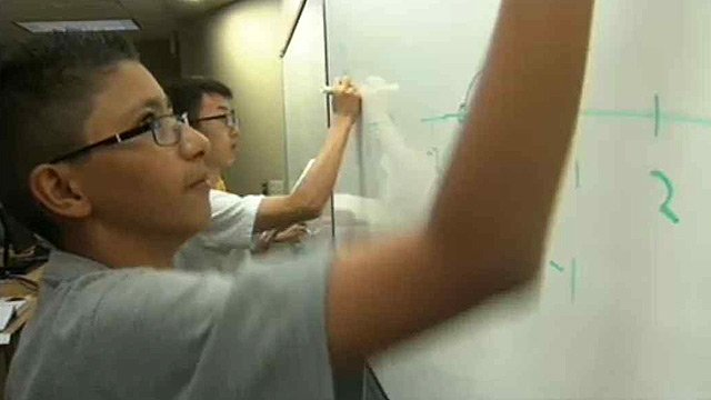 Javier takes to the white board with classmates.
