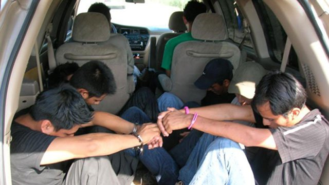 Eight people identified by deputies as illegal immigrants sit in a van after it was stopped Thursday.