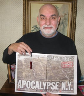 Sandy survivor Jim Pantaleno poses with flashlight and newspaper article about the storm
