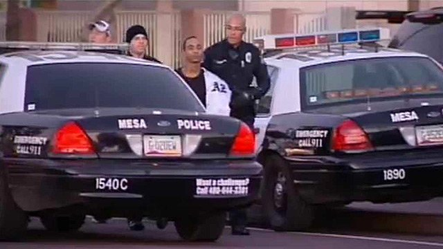 (Source: CBS 5 News) Mesa police officers escort a shooting suspect who held police at bay Tuesday morning to a waiting patrol car.