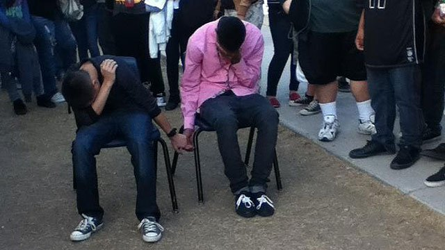 (Source: Facebook) A couple of Westwood High School Warriors were humbled after a fight and now pictures of the high school boys holding hands as punishment and covering their heads are all over Facebook.