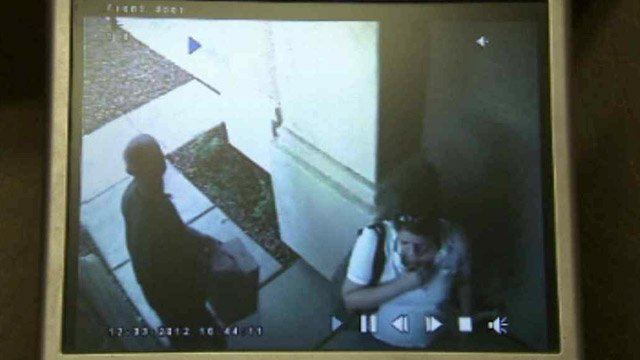 (Source: CBS 5 News) Surveillance video shows the suspected thieves on the front porch, the man carrying the package from the porch to around the house.
