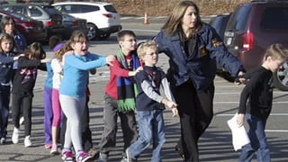 (Source: Newtown Bee/Shannon Hicks) CT. State Police lead children from the Sandy Hook Elementary School in Newtown.