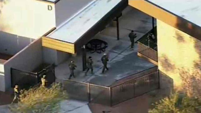 (Source: CBS 5 News) Police comb the campus of Cocopah Middle School on Wednesday.
