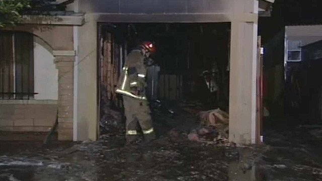 (Source: CBS 5 News) A Phoenix firefighter combs through the ashes of a garage that caught fire early Thursday morning.