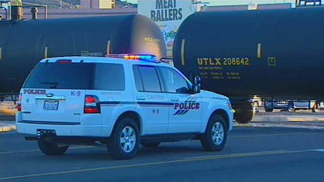 (Source: CBS 5 News) A Tempe police cruiser sits at the crossing where a train and minivan collided Wednesday morning.