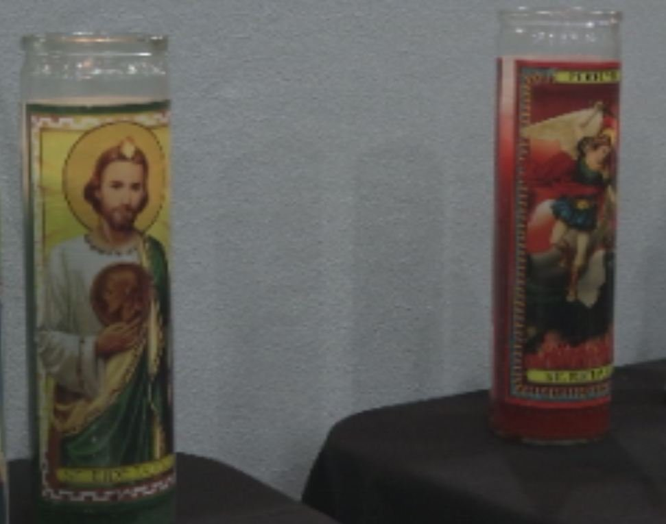 (Source: CBS 5 News) A candle of St. Jude sits next to one of St. Michael