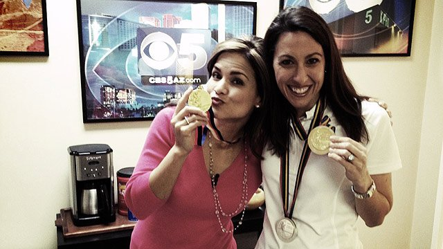 (Source: CBS 5 News) Nicole Rites, left, and Janet Evans show off three of Evans' medals.
