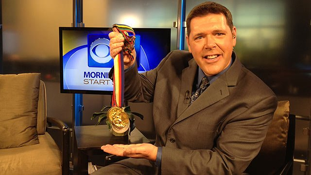 (Source: CBS 5 News) No, this isn't Paul Horton's medal haul, he's just acting as a stand for swimmer Janet Evans' medals.