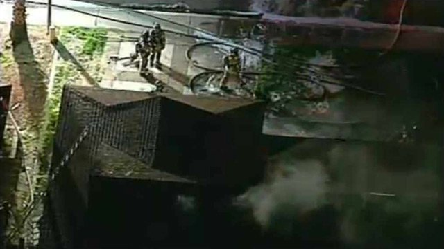 (Source: CBS 5 News) Gilbert firefighters work the hoses while smoke pours from a hole cut in the roof during a house fire Friday morning.