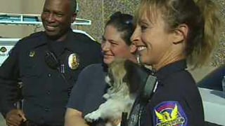 "Phoenix police officers pose with Jessica and ""Buddy"" (Source: KPHO-TV)"