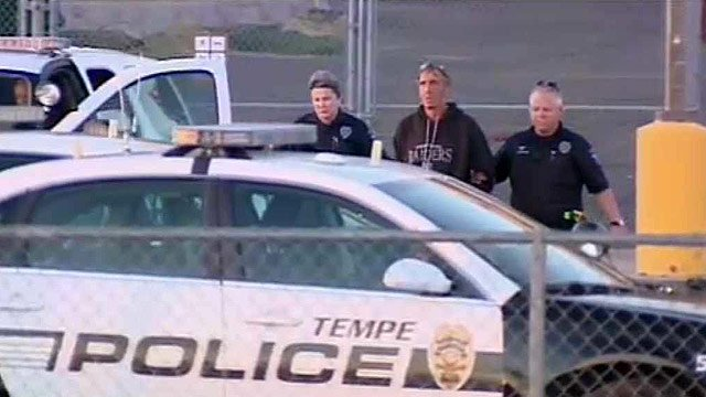 Tempe police escort a man to their cruiser after he barricaded himself in the ASU football stadium Thursday morning. (Source: CBS 5 News)