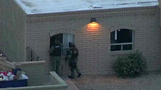 Federal agents peer into a suspected drop house for illegal immigrants in Phoenix on Tuesday morning. (Source: CBS 5 News)