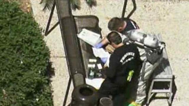Phoenix firefighters inspect documents taken from Sen. Jeff Flake's Phoenix office Wednesday morning. (Source: CBS 5 News)
