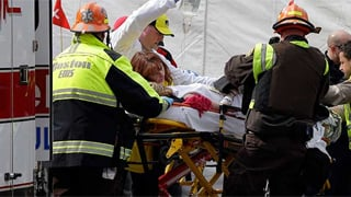 An injured person is loaded into an ambulance in the aftermath of two blasts which exploded near the finish line of the Boston Marathon. (Source: Elise Amendola, AP)