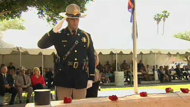 A DPS officers salutes fallen DPS officers at a memorial Monday. (Source: CBS 5 News)