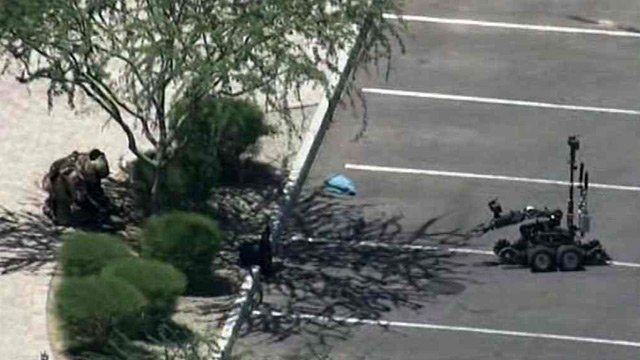 A Maricopa County bomb squad member and the MCSO bomb robot near a suspicious package at the Justice Court in Buckeye on Monday morning. (Source: CBS 5 News)