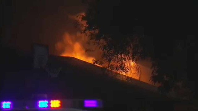 Flames shoot through the roof of a Mesa home left in disarray by its previous tenants. (Source: CBS 5 News)