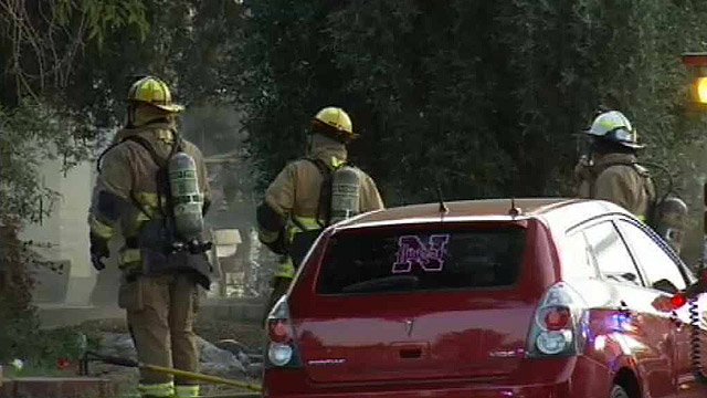 Firefighters outside the house contemplate their next move. (Source: CBS 5 News)