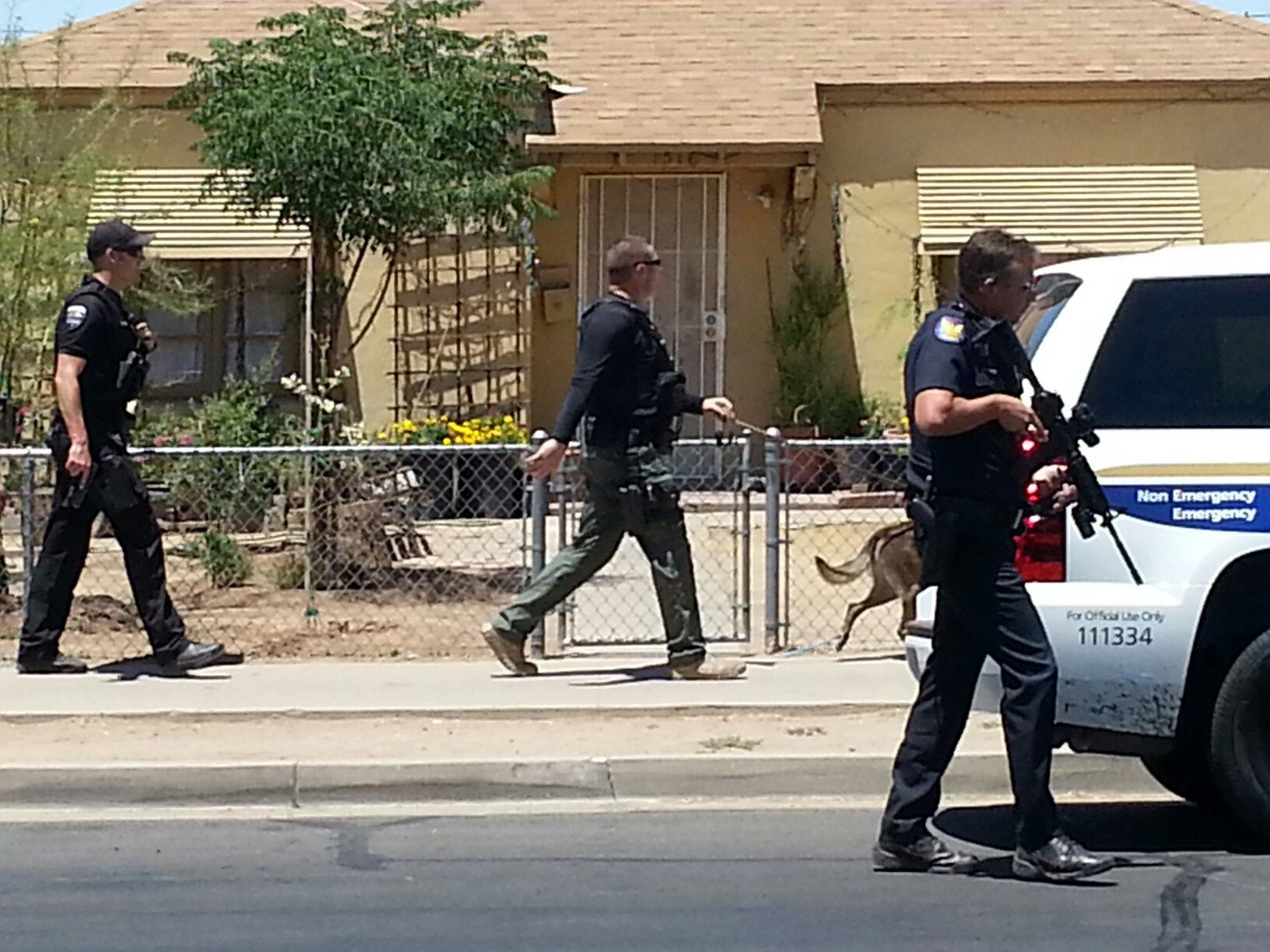 Police officers and a canine work houses near 16th Avenue and Roosevelt Street looking for suspects who led officers on a high-speed chase into Phoenix. (Source: CBS 5 News)