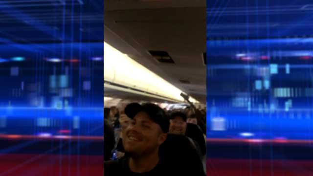 An image from a YouTube video shows passengers laughing off an hours-long delay June 9, 2013. (Source: YouTube/Dustin Kaelberer)