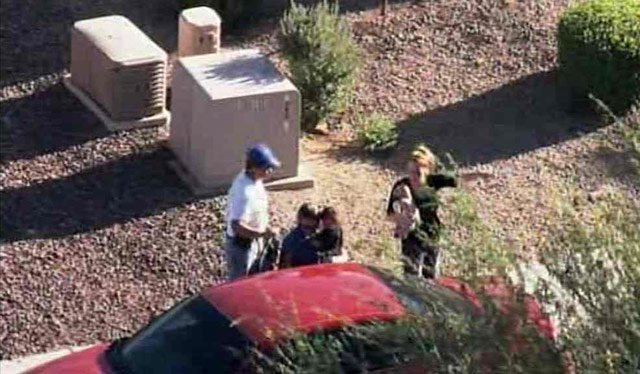 An MCSO detective places the child in a car while the mother, right, holds a stuff animal. (Source: CBS 5 News)