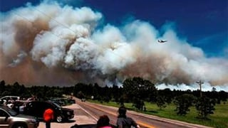 A fire-fighting slurry plane makes a pass in preparation to drop its load on a wildfire in the Black Forest area north of Colorado Springs. (Source: AP Photo/Brennan Linsley)