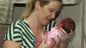 Jaime Varley holds one of the triplets. (Source: CBS 5 News)
