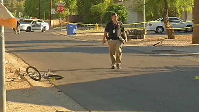 A Phoenix police officer looks for clues at the scene of a shooting that killed a bicyclist. (Source: CBS 5 News)