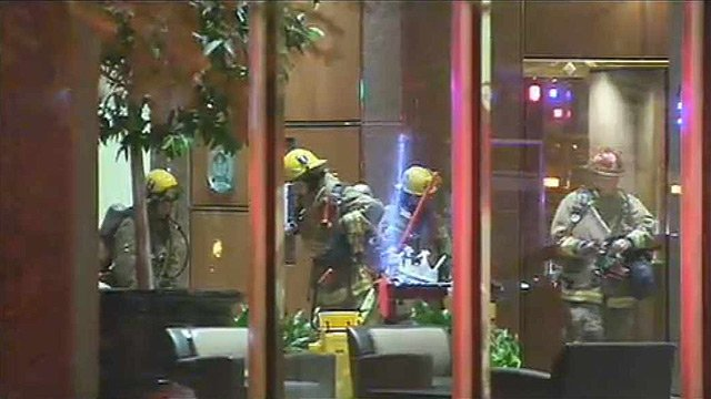 Phoenix firefighters assemble in the lobby of a Phoenix high-rise office building after small fire was reported Thursday night. (Source: CBS 5 News)