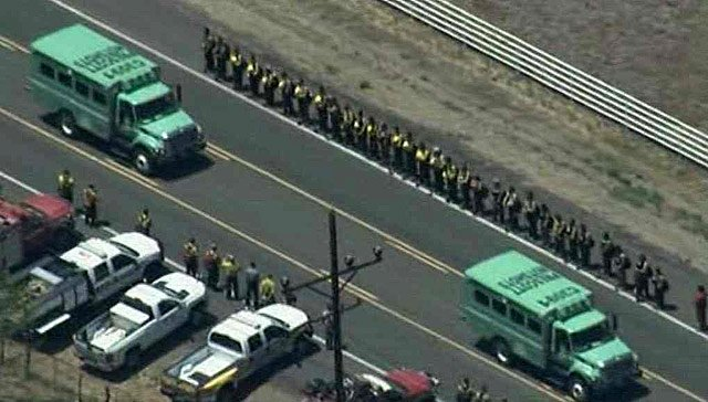 Firefighters line the highway leading from Yarnell as the vehicles used by fallen Granite Mountain Hotshot crew members to fight the Yarnell Hill Fire are driven back to their base in Prescott. (Source: CBS 5 News)