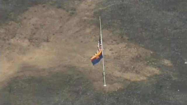 A flagpole marks the site where 19 Granite Mountain Hotshots were killed while fighting the Yarnell Hill Fire. The memorial is visible from U.S. Highway 89, which reopened Wednesday. (Source: CBS 5 News)
