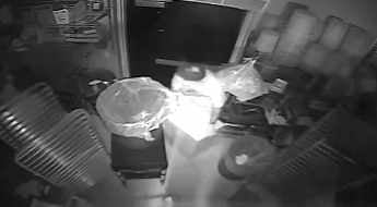One of the suspects reaches for and pulls the safe out the door. (Source: Mesa Police Department)