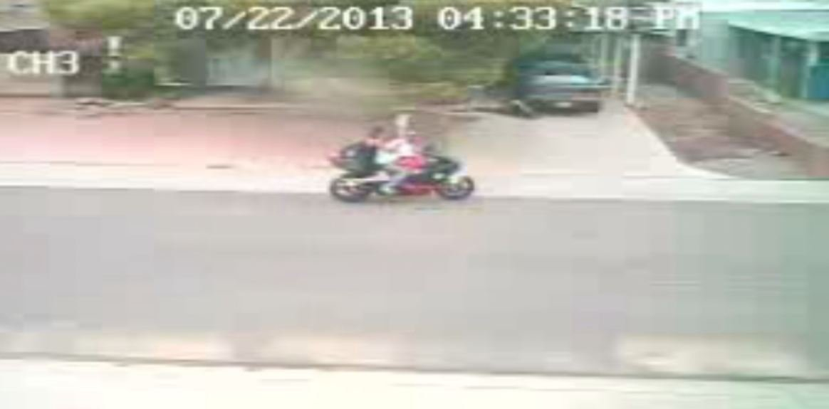 This still shot shows two people leaving on a motorcycle. The victim is on the ground near the green car.