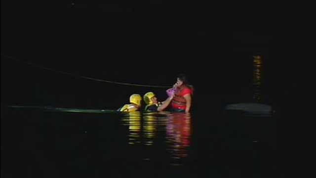 Phoenix firefighters secure a woman who drove her car into a canal early Wednesday morning. (Source: CBS 5 News)
