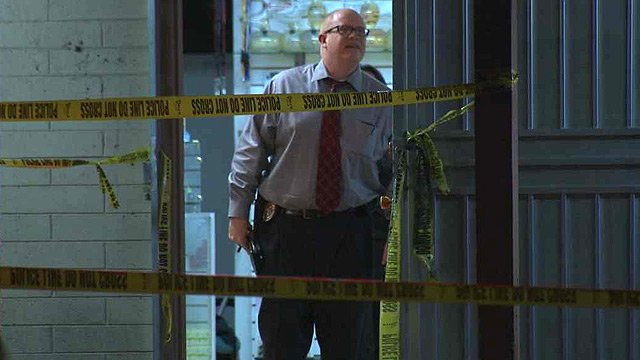 A Scottsdale police investigator looks for clues after a shooting at a Scottsdale smoke shop Tuesday evening. (Source: CBS 5 News)
