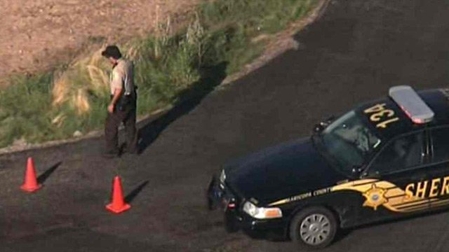 A Maricopa County sheriff's deputy places orange cones in a Buckeye roadway near where three children were struck by a car Tuesday morning. (Source: CBS 5 News)