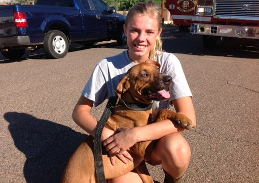 Missy Grinstaff sits with Buck, the family's 10-month-old dog whose barking woke the family and alerted them to an attic fire in their home. (Source: Phoenix Fire Department)