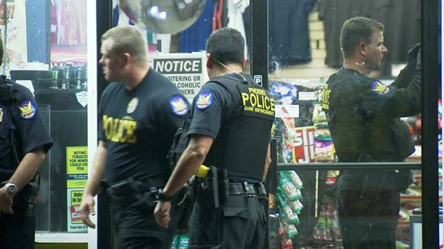 Phoenix police officers survey Eddie's Quick Stop while serving search warrants as part of an investigation into gang activities. (Source: CBS 5 News)