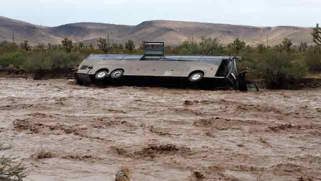 Floodwaters sweep tour bus into wash. (Source: Northern Arizona Consolidated Fire District)