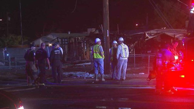 Firefighters and gas workers stand in front of a Peoria house that was destroyed in a fiery explosion in which two people were burned and injured. (Source: CBS 5 News)