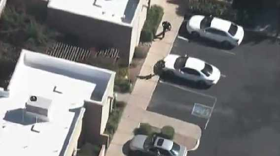 Aerial of police chasing after woman suspect just before her arrest