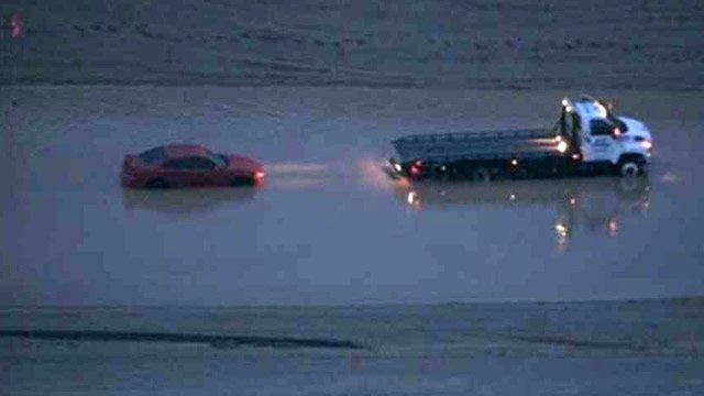 A car is stuck on a flooded stretch of road near Loop 303 and Glendale Avenue. (Source: CBS 5 News)