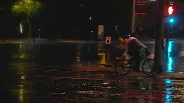 A bicyclist negotiates wet roads in the East Valley early Friday morning. (Source: CBS 5 News)