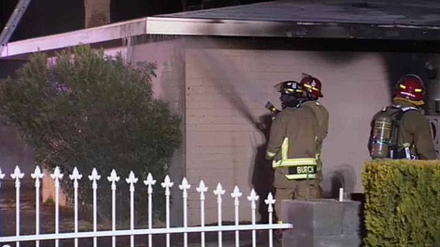 Glendale firefighters spray water on a house in which a family's possessions were destroyed by fire Tuesday. (Source: CBS 5 News)