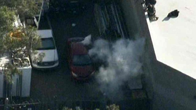 Tear gas pours from a red sedan before the driver gave himself up to Mesa police Monday morning. (Source: CBS 5 News)
